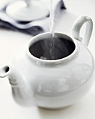 Pouring boiling water into white teapot