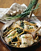 Fish fillets with ginger, carrots, spring onions in pan