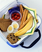 Lunch box with banana, cookie, egg, bread etc.