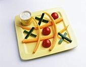 Vegetable sticks, tomatoes & yoghurt dip as Noughts and Crosses