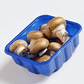 Chestnut mushrooms in blue plastic punnet