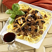 Spaghetti Topped with a Sausage and Mushroom Sauce with Basil Garnish, Red Wine