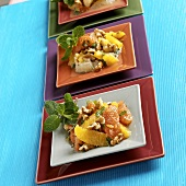 Citrus Walnut Salad Served on Three Colorful Square Plates, Mint Garnish