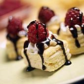 Puff pastry slices with cream, chocolate sauce & raspberries