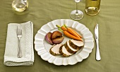 Sliced Pork Tenderloin Served with baby Carrots and Shallots on a White Plate