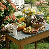 Buffet of grilled food and salads on garden table
