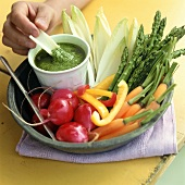 Hand dipping celery into herb dip on raw vegetable platter