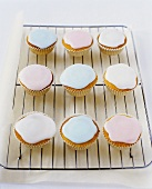 White Cup Cakes with Pastel Blue, Pink and White Icing on Cooling Rack