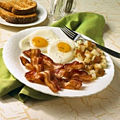 Breakfast Plate of Fried Eggs with Bacon and Home Fries on White Plate with Fork