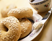 Oat Bagels on a Plate with a Knife with Cream Cheese, Cup of Coffee