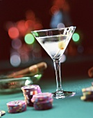 A Martini glass, casino chips and a cigar on an ashtray in the background