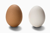 Two hen's eggs, one brown one white, against a white background