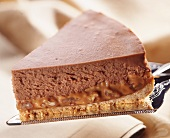 A slice of chocolate-caramel cheesecake on a cake slice