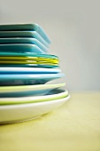 Blue and green plates of various sizes, in a pile