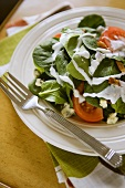 Spinach salad with tomatoes, blue cheese & yoghurt dressing