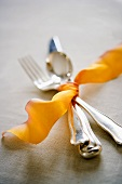 Cutlery tied together with orange ribbon