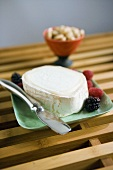 Soft cheese and berries on green plate with cheese knife