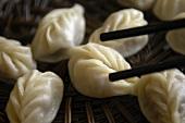 Chopsticks taking dumpling out of bamboo steamer (Asia)