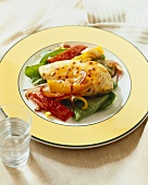 Glazed Chicken Breast with Tri-Colored Bell Peppers on a Plate, Glass of Water