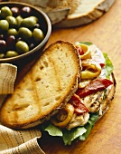 Grilled Chicken Sandwich with Roasted Peppers and Lettuce, Bowl of Mixed Olives