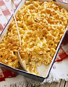 Baked Macaroni and Cheese in a Casserole Dish with Scoop Removed, Serving Spoon