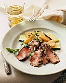 Sliced Herb Crusted Steak Cooked Rare on a Plate with Sliced Vegetables; Fork and Knife