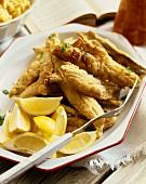 Fried Fish Fillets on a Platter with Lemon Wedges; Serving Fork