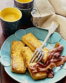 Three French Toast Sticks on a Plate with Bacon and a Fork; Cup of Orange Juice