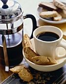 Cup of Coffee on Saucer with Biscotti; Percolator and Plate of Biscotti