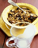 Granola with Raisins in a Yellow Bowl with Spoon; Empty Milk Pitcher