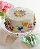 Easter Cake Decorated with Easter Candies on a Cake Plate; Stack of Plates with Forks