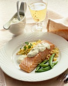 Poached Salmon Topped with Cream Sauce Served with Snap Peas and Rice; Glass of White Wine