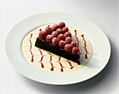 Slice of Chocolate Tart Topped with Fresh Raspberries in a Decorative Sauce on White Plate