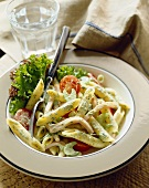 Penne Pasta with Vegetables in a Pesto Sauce in a Bowl with a Fork