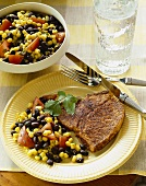 Spicy Pork Cutlet Served with Black Bean and Corn Salad on a Plate, Fork and Knife, Glass of Water