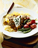Beef Stew Over Egg Noodles with Sour Cream; Snap Peas and Red Potatoes on a Plate with Fork