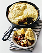 Black Bean Casserole with Corn Bread Topping in a Skillet and in a Bowl; White Background