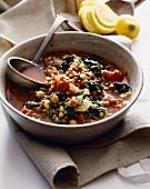Bowl of Lentil Vegetable Stew with a Ladle; Sliced Lemon