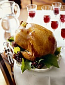 Whole Roasted Turkey on a Dining Table with Glasses of Wine