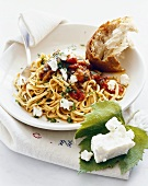 Plate of Pasta with Tomatoes and Goat Cheese; Piece of Crusty Bread