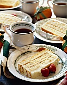 Slices of Layered Almond Cake on Plates with Cups of Coffee