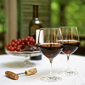 Two glasses of red wine, red wine bottle, corkscrew, grapes