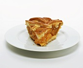 Piece of peach pie on white plate