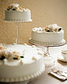 Three white wedding cakes decorated with flowers