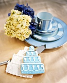 Two Wedding Cake Cookies Next to a Blue Place Setting with Hydrangeas