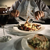 Man with spattered napkin tucked in shirt eating chicken