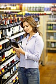 Woman Reading Label on Wine Bottle in a Grocery Store