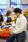 Man emptying basket at supermarket check-out