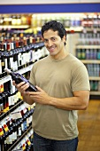 Smiling man holding bottle of wine in a supermarket