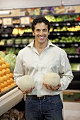 Man holding two melons in a supermarket